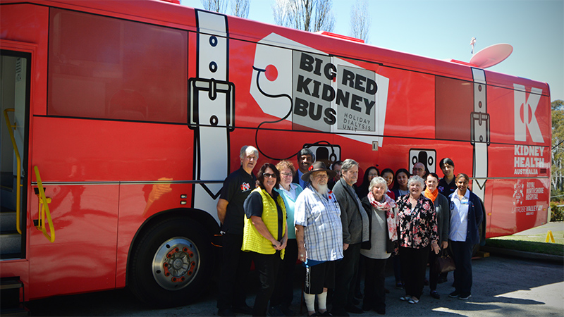 Staff and patients standing next to the Big Red Kidney Bus