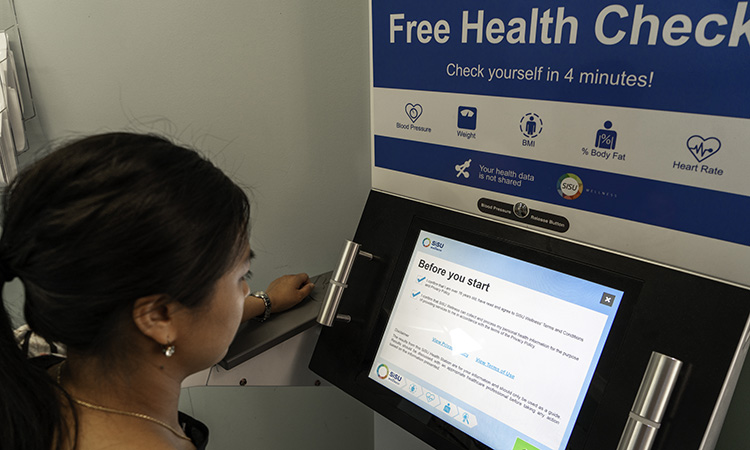 Woman using health check station